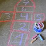 הילדים מציירים קלאס בגירי מדרכה פרימו ולאחר מכן משחקים קלאס.
